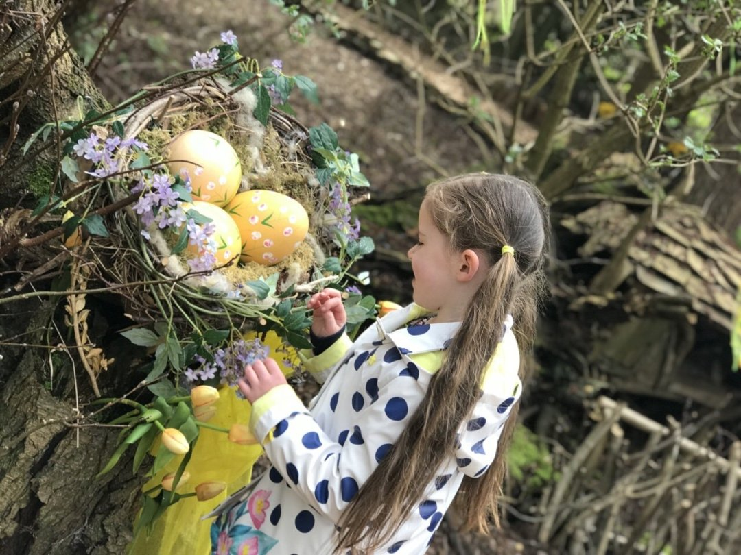 Child standing looking at Easter eggs in the forest. Easter Train at Audley End