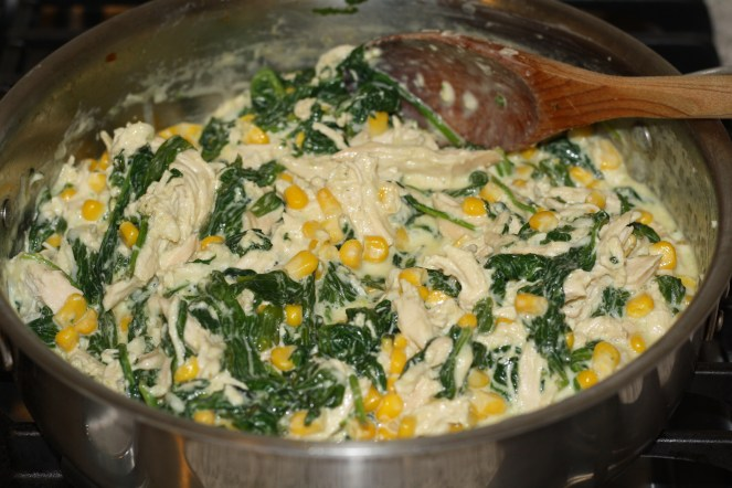 Pulled chicken, spinach, corn, cheese and heavy cream in a stainless steel pan with a wooden sppon