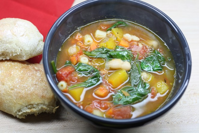 Charcoal bowl of vegetable heavy minestrone soup and two rustic dinner rolls on a red napkin