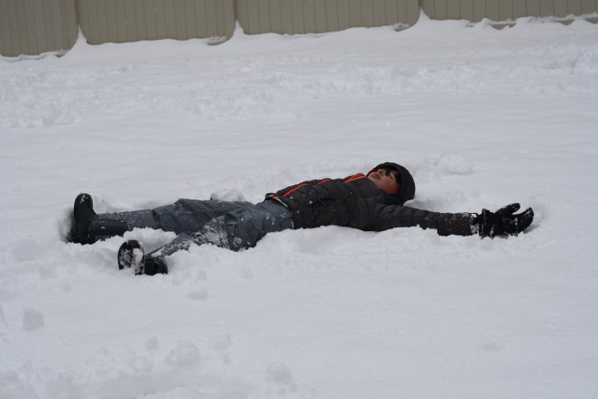 boy laying in snow making a snow angel