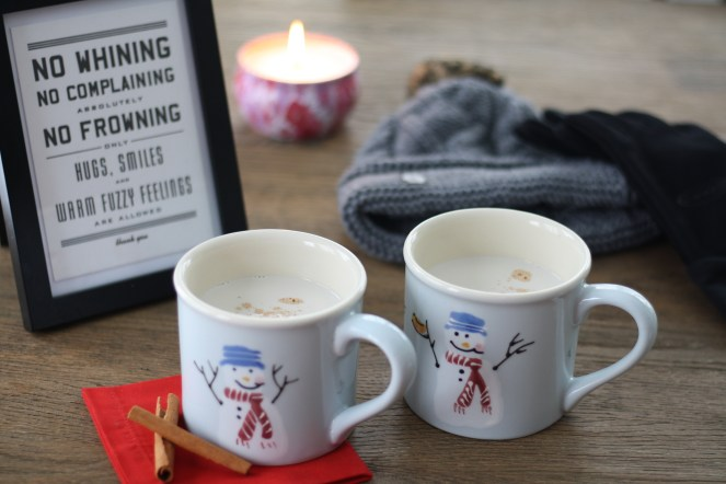 "Two light blue snowman mugs filled with vanilla almond steamer on top of a red napkin with cinnamon sticks. Hat, gloves and a pink flowered candle in the background on wooden table, and a framed sign that reads, ""No Whining, No Complaining, Absolutely No Frowning. Only Hugs, Smiles and Warm Fuzzy Feelings Are Allowed. thank you."""