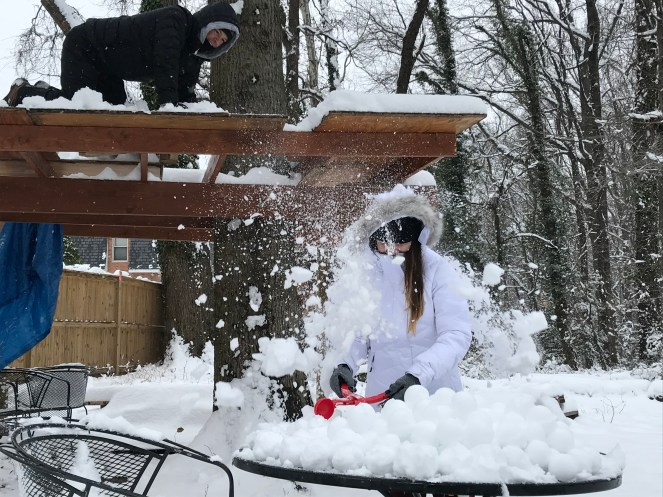 Father on treehouse platform dumping snow down onto daughter who is making snowballs