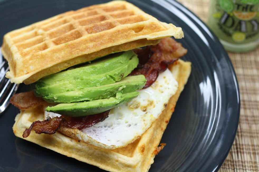 Two waffles with a fried egg, two bacon slices and sliced avocado sandwiched in the middle. All on a charcoal colored plate on a brown woven placemat.