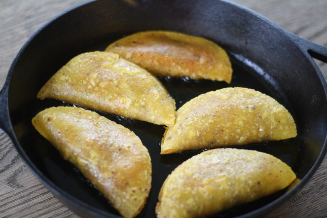 Cast iron skillet with five tacos inside, all facing upward.