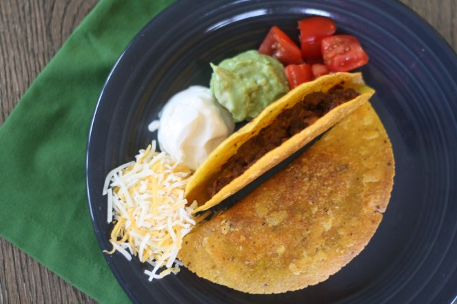 Two cooked tacos on a charcoal colored plate. On the plate to the left of the tacos is shredded cheese, sour cream, guacamole, and diced tomatoes. The plate is on a wooden table with a green napkin underneath.