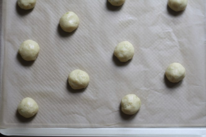 10 cookie dough rounds on a parchment-lined baking sheet