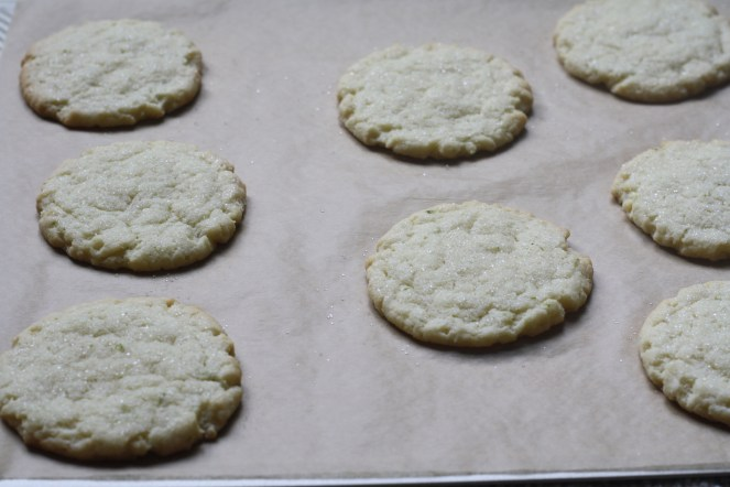Eight baked cookies are on a baking sheet lined with parchment paper.