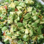 Large white bowl of kale taco salad, lots of avocados on the top