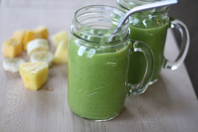 Two glass ball jars with handles filled with Beginner's Luck Green Smoothie and stainless steel straws. Chopped pineapple, mango and banana are on the side.