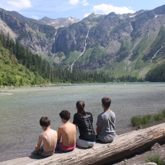 Four kids sitting on a log facing Avalanche Lake