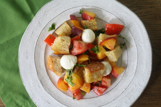 Gray plate of Peach Panzanella on top of a green napkin
