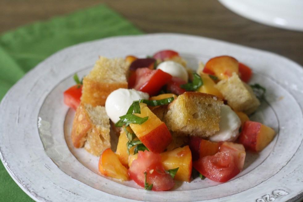Peach Panzanella atop a light gray plate with a green napkin