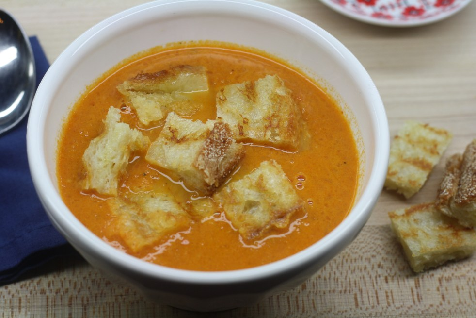 White bowl of tomato soup topped with grilled cheese croutons.