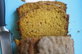 freshly baked pumpkin bread slices on a blue cutting board