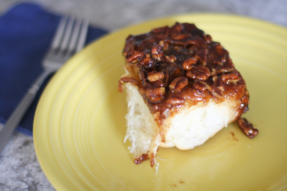 One sticky bun on top of a yellow plate, fork and navy cloth napkin in the background