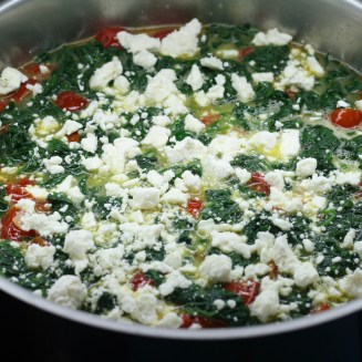 Sauté pan with tomatoes, shallots, spinach, egg and feta
