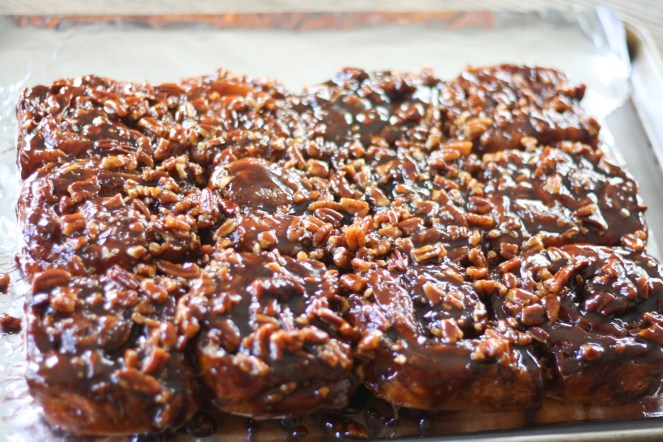 Dozen sticky buns inverted on foil-lined sheet