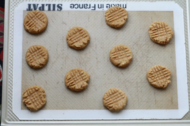 Pre-baked peanut butter cookies on silicone mat on baking tray