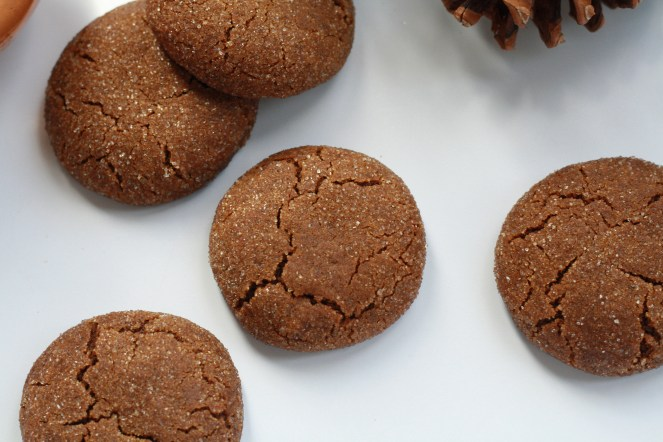 Five baked molasses cookies on a white surface