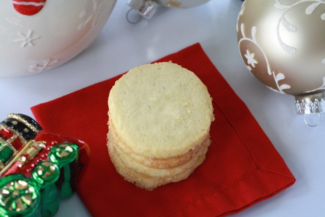 Stack of four vanilla sables on a red cocktail napkin, surrounded by various Christmas ornaments