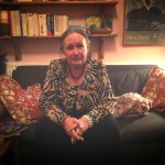 Dolores Fitchie, sitting on a sofa in her living room, surrounded by books and art.