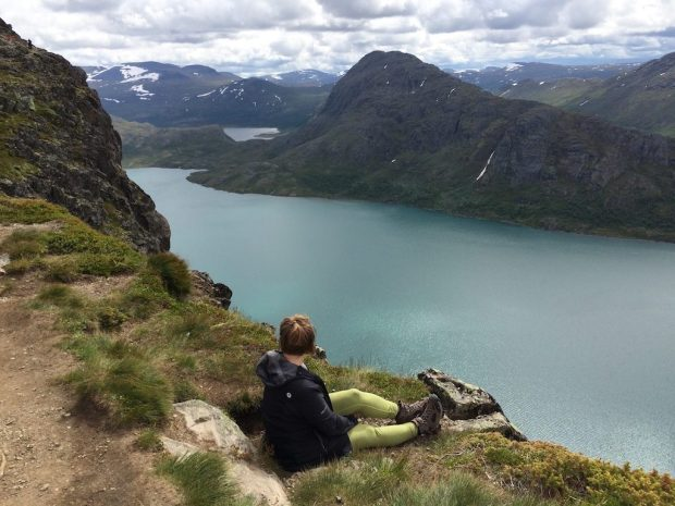 Abbie sitting at the edge of a mountain in Norway's Jotunheimen National Park