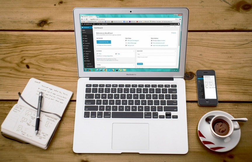 In the centre is a laptop. A mobile is on the right, a cup underneath the mobile. On the left, is a notebook and pen.
