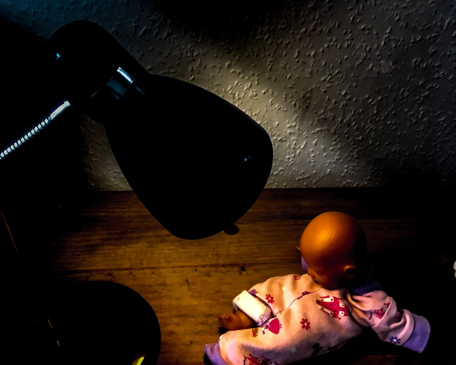 A doll under a lamp, being interrogated. Feature image for Personal Independence Payment interrogation (PIP assessment).