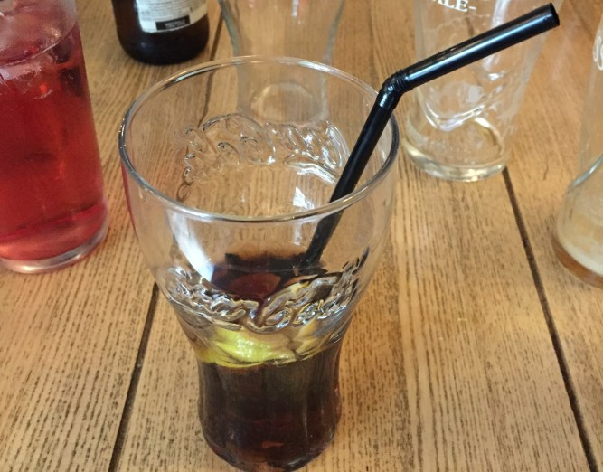 Plastic straw in a glass of coke (or Cola Cola)