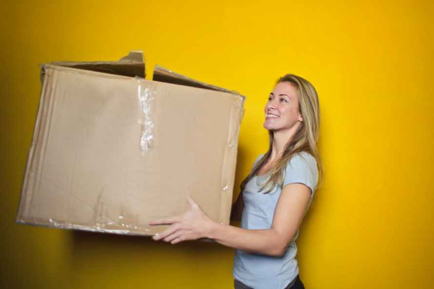 woman holding cardboard box, moving in. Feature image of moving in student halls