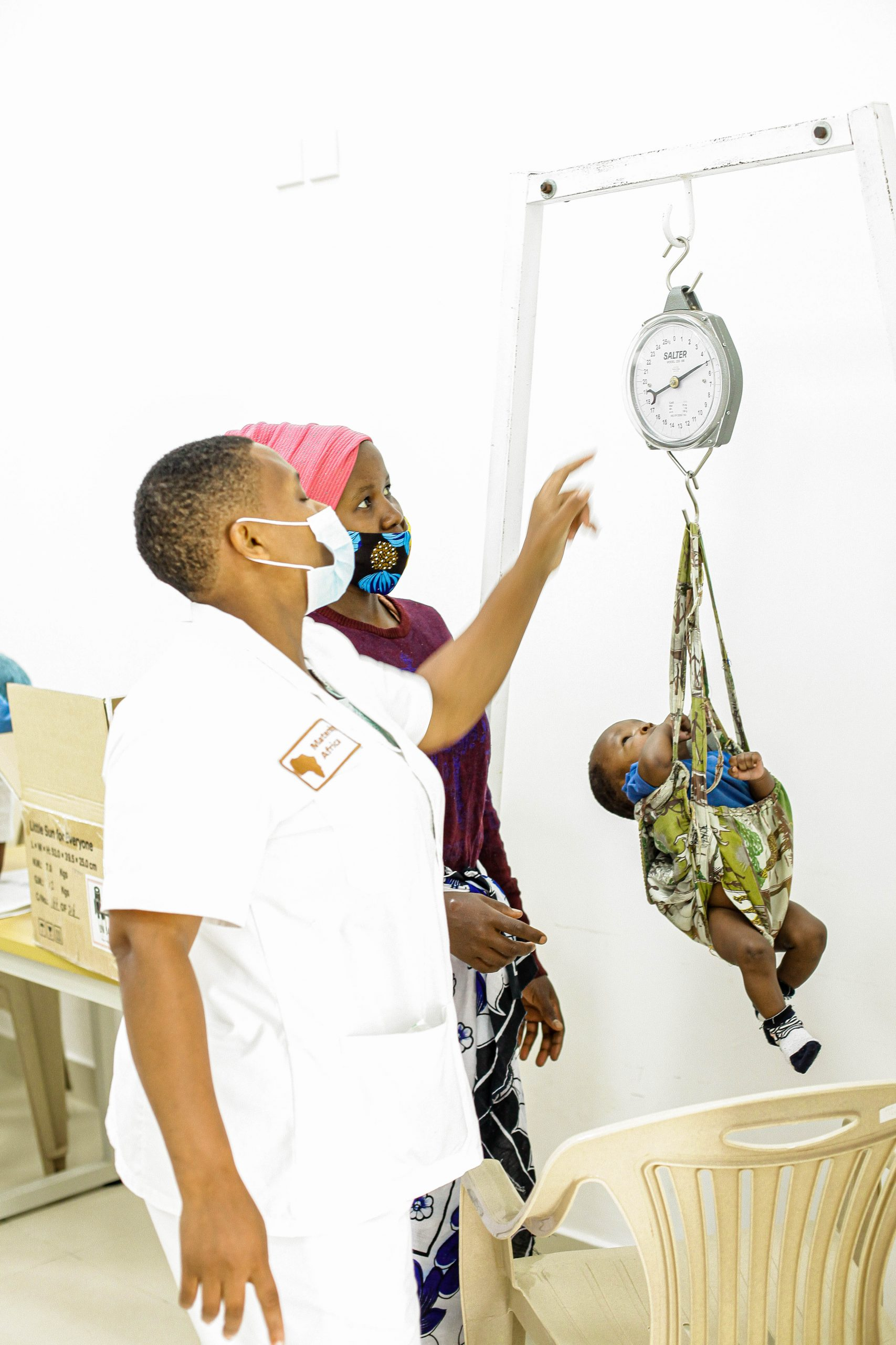 A health worker weighing a small child