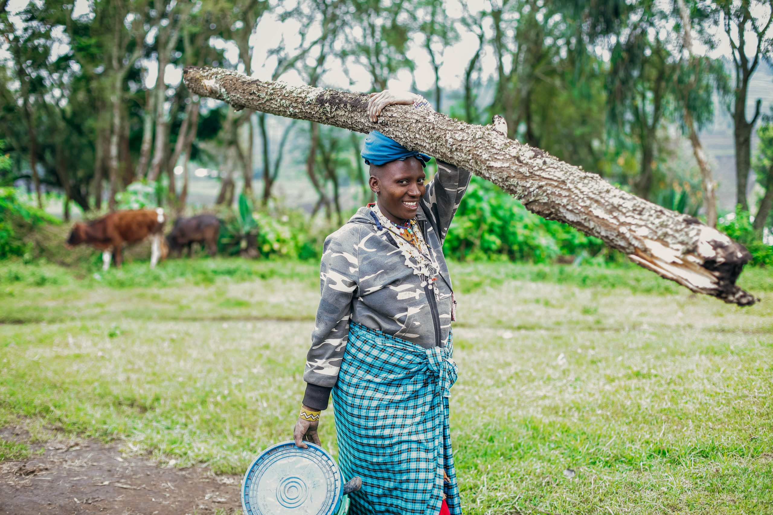A woman in Africa carrying wood and food to her community