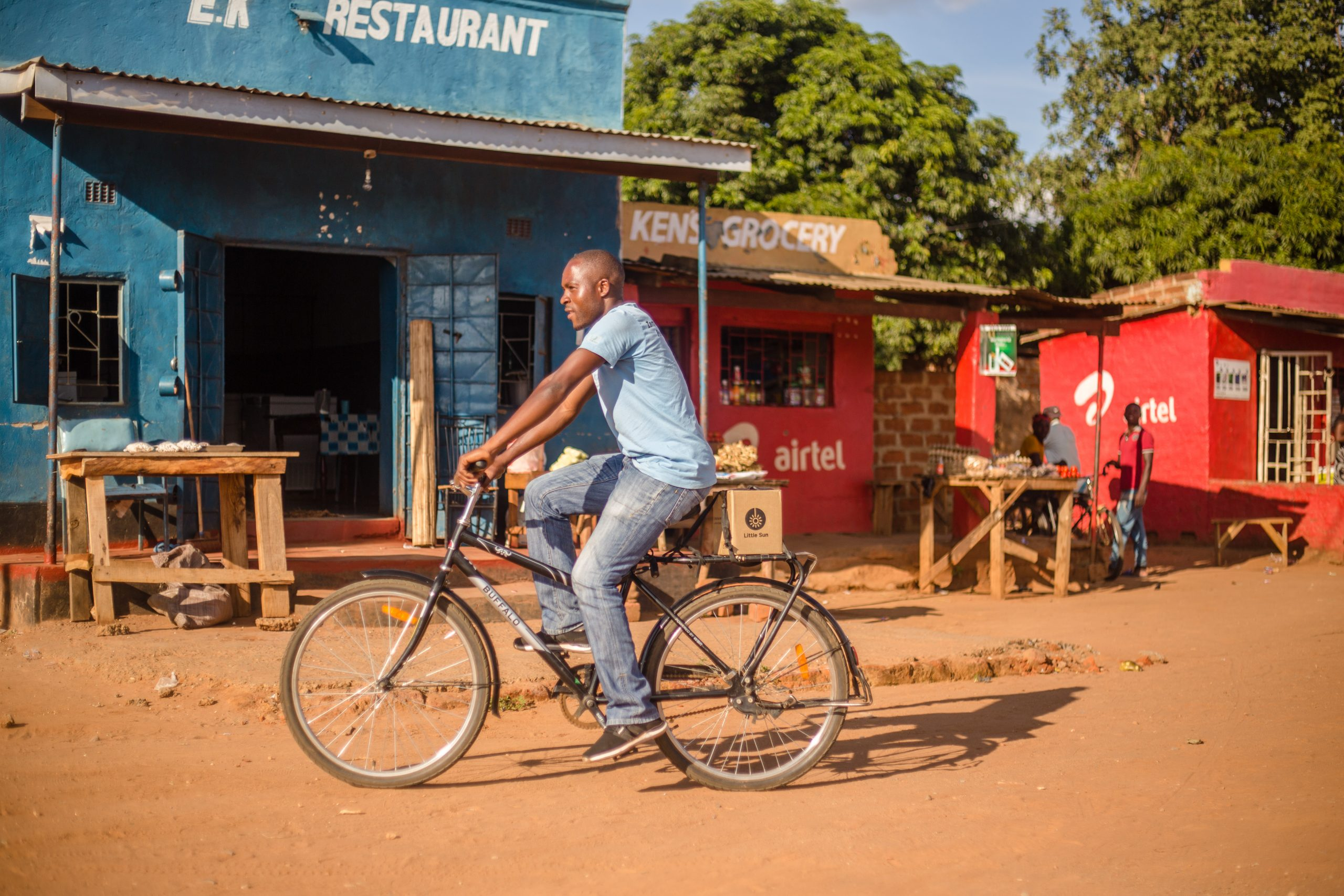 A man on the bike transporting Little Sun solar lamps for food security programs