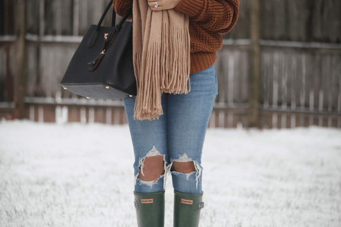 Ripped denim, green hunter boots, and an oversized scarf help style this outfit for winter.