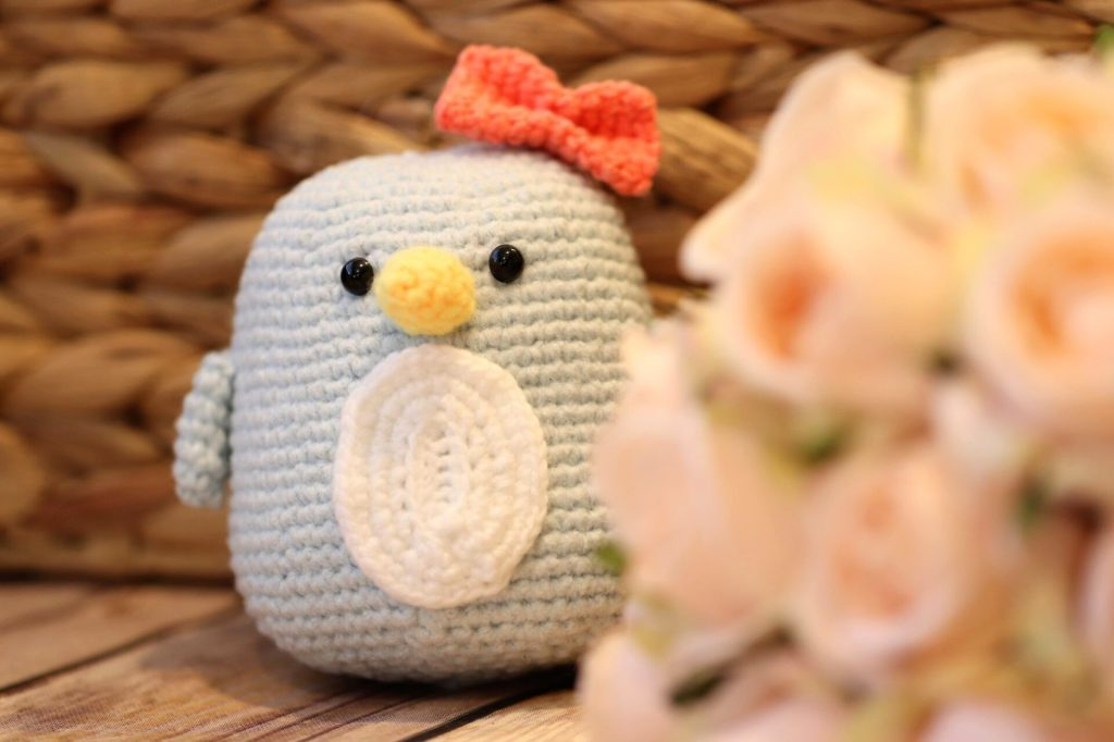 amigurumi penguin in background with bouquet of flowers in the foreground