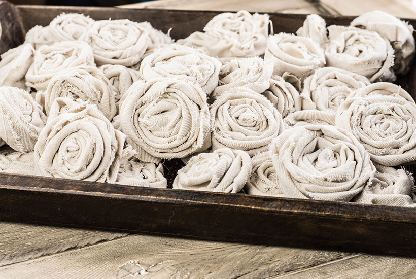 A tray full of crafted canvas roses