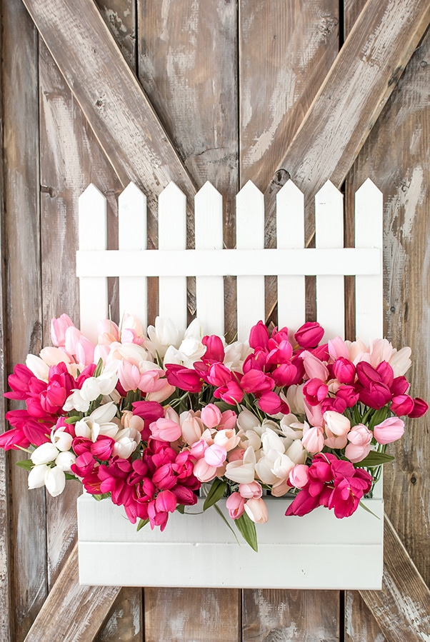 White picket fence wreath filled with pink and white tulips