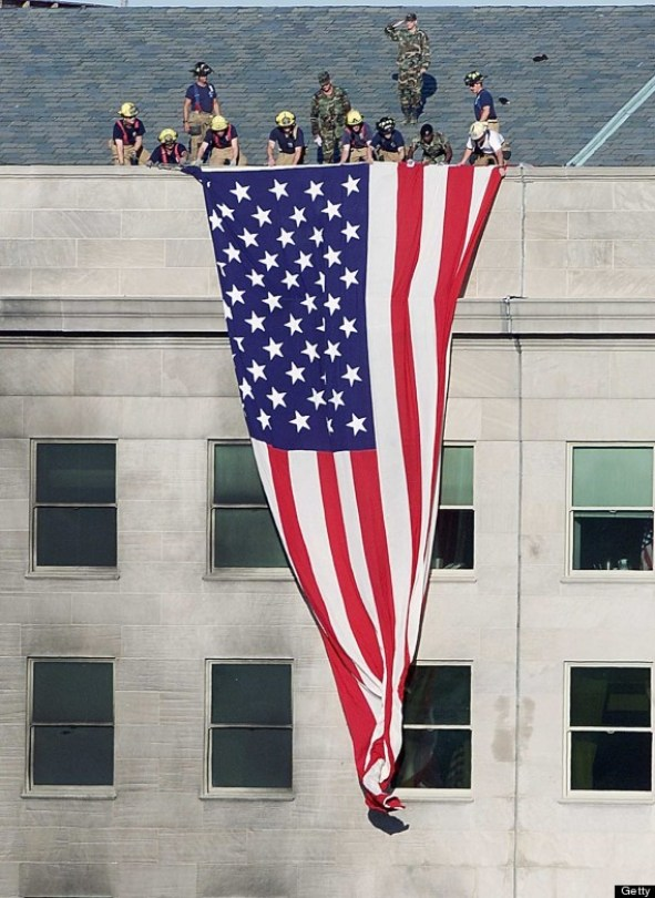 Firefighters and soldiers unfurl an American flag from the roof of the damaged side of the Pentagon 12 September 2001 in Washington, DC.  A hijacked airplane crashed into the Pentagon 11 September 2001 causing extensive damage and loss of life.    AFP PHOTO/Luke FRAZZA (Photo credit should read LUKE FRAZZA/AFP/Getty Images)