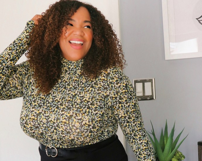 A Black Woman with Curly Hair in a Pencil Skirt with a turtleneck