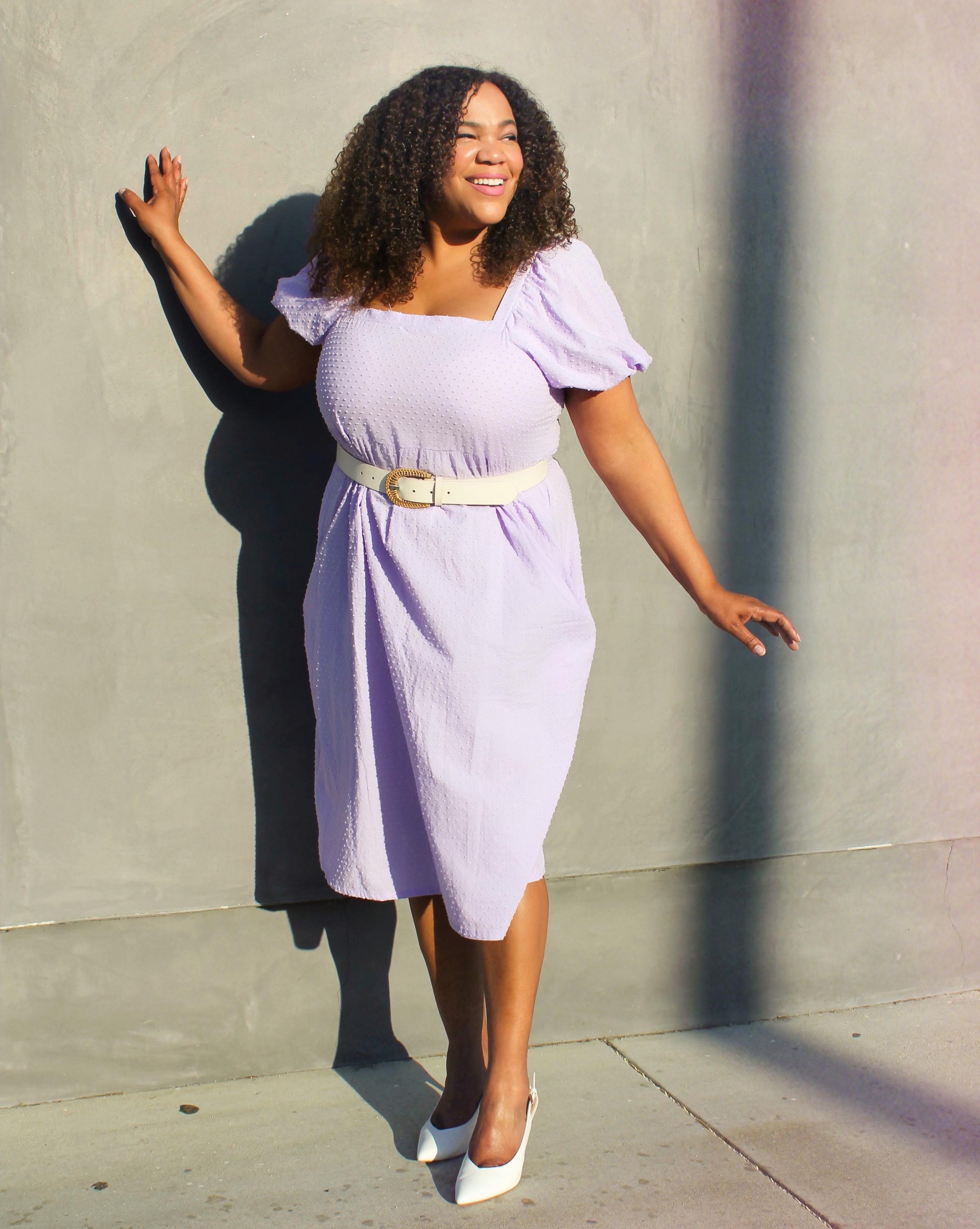 A black woman in a purple dress