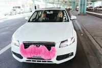 A white car with a pink mustache attached to it's front grill with two people riding.