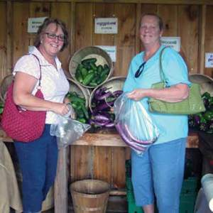Two women stand in front of a vegetable stand