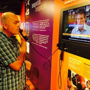 A man holds a phone to his ear as he listens to a video in an exhibition
