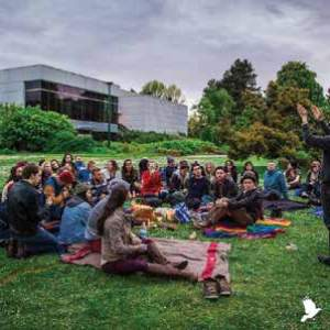 A group of people sit outside on a grassy area an dlook at a person presenting