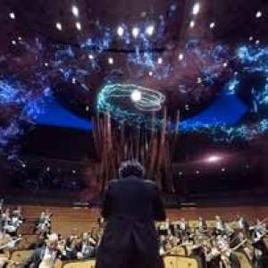 An orchestra plays with the conductor in teh foreground and a light show in the background