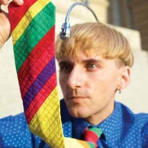A man holds his multi-colored rainbow tie up while an antenna like apparatus extends from his head.