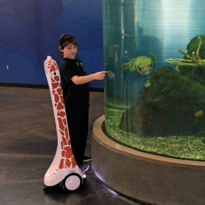 A young man stands next to an aquarium tank with a telepresence robot designed to with giraffe spots