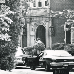 Black and white image of police cars parked in front of the mansion with one gentleman standing near the front door gesturing with what appears to be a walkie talkie in his hand.