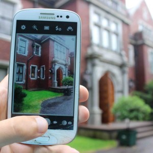 Image of someone holding up their cell phone to take a picture of the outside of Glensheen mansion. You can see the house blurry in the background and clear on the phone screen in the image.