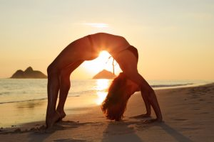 a confident girl doing yoga on the beach after full bikini waxing in Tallahassee